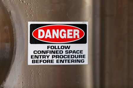 DANGER, FOLLOW CONFINED ENTRY PROCEDURE BEFORE ENTERING, warning vinyl sticker sign on stainless steel cold industrial tank, with copy space