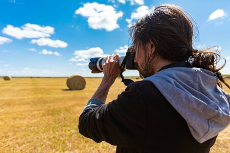 Male photographer with long hair shooting bales of hay in the countryside with professional DSLR camera and expensive looking long lens.