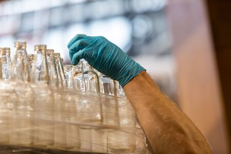 a lot of new beer white glass empty bottles, caucasian man hand with blue Rubber glove holding one bottle, selective focus close up view Banque d'images