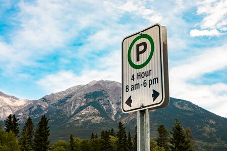 white sign with a green circle, 4 hours parking on specific times 8 am - 6 pm sign, against mountains and the blue sky, British Columbia, Canada Standard-Bild