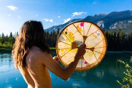 Un primer plano y una toma trasera de un baterista chamánico tocando un tambor sagrado de estilo indígena en la naturaleza, de pie junto a un lago tranquilo en busca de iluminación Foto de archivo