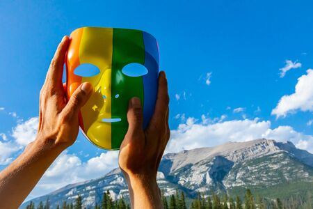 A man is seen holding a colorful mask with the colors of the peace flag up against a backdrop of the Rockies in Alberta