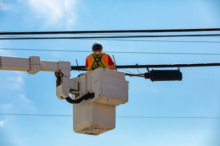 A low angled shot of a man at work in a mobile elevating work platform, MEWP or cherry picker, repairing and maintenance of overhead power cables