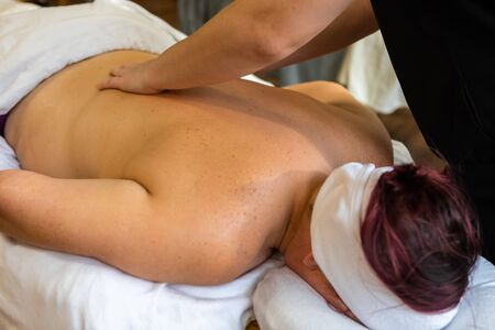 A closeup shot as a caucasian woman with red hair lies face down on a massage table as masseuse manipulates soft tissue  Stock Photo