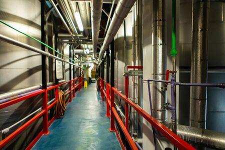 passageway between metal tanks, vessels and pipes, Modern brewhouse brewery beer factory industrial machines, processes of brewing beer