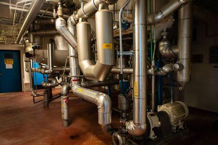 le système de tuyauterie sous les réservoirs et les cuves, les tuyaux et pompes métalliques en acier inoxydable, avec des signes de prudence chaude, le pré-sirop de moût, l'injection de sirop, la vapeur Banque d'images