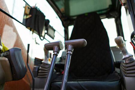 Vista de ángulo bajo dentro de la cabina de una miniexcavadora, que muestra las palancas de control para operar los brazos hidráulicos con el asiento del conductor en el fondo y espacio de copia