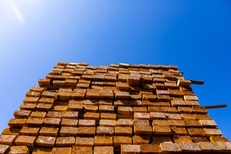 A bright sunny glare is view from below, shining over a large pile of treated wood planks, 4 by 2 boards used in construction of stud walls, with copy space