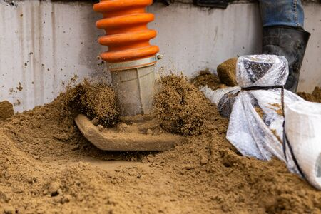 A closeup view on the metal plate of a vibrating rammer, with sand jumping in air from the heavy action of machine, groundwork and preparation.