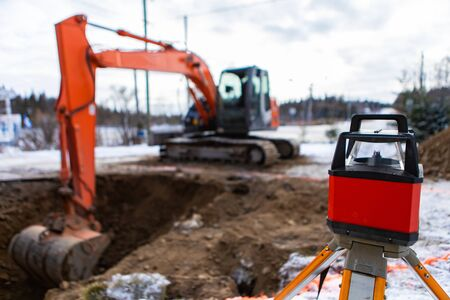 A close up view of a laser level with tripod set up on a building site. with blurry excavator using backhoe bucket to dig ditch for septic tank Imagens