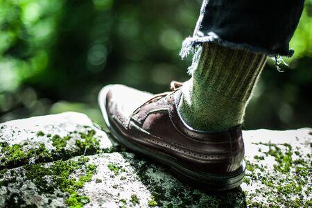 Tritt auf den Rand eines Felsens, der mit grünem Moos bedeckt ist. Selbstbewusster junger Mann, der gut aussehende Schuhe mit grünen Hippie-Wollsocken und blauen, zerrissenen Jeans trägt.