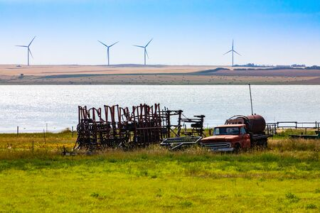 A wide angle view of outdated rusty farm equipment stored in a waterfront field. Old truck and tractor attachments by a lake with wind turbines in background Stock Photo