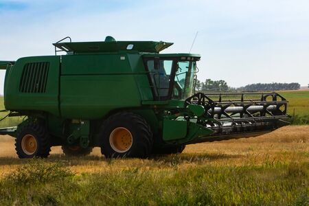 A close up and side view of a large green combine harvester, details of the cutter bar, reel and thresher unit, designed to harvest grain cops