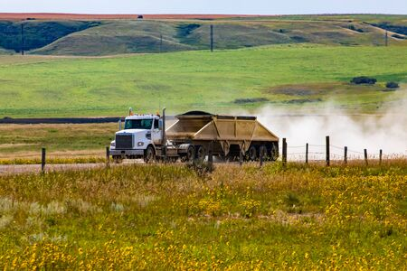 A large transport truck pulls heavy trailer of farm goods on a rural road in truck Saskatchewan, Canada. Dust rises from road behind large vehicle Reklamní fotografie