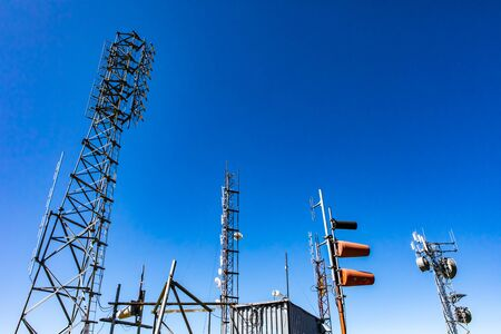 A low angle view of GPS radio communication lattice steel towers and cellular network base station for transmission and receival of broadcast signals
