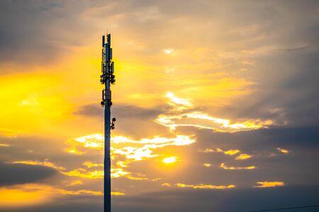 Una vista de gran angular de una torre de sitio celular monopolo al atardecer. Estación base celular silueta retroiluminada dorada con nubes dispersas y espacio de copia Foto de archivo