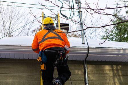 A professional domestic service engineer is seen climbing a ladder to reach a snow covered roof during the installation of fiber optical cabling