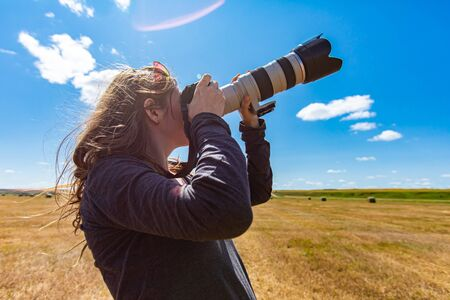 sunny day in the countryside, and a woman in an agricultural field pointing expensive camera and long telephoto lens towards the sky. Lens flares. Foto de archivo