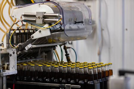Dark beer glass bottles with yellow cap, capping bottle machine, conveyor belt line, Craft brewery factory microbrewery bottling