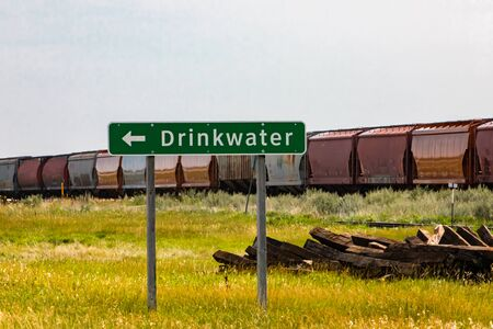 Information Road Green Sign with Left arrow to Drinkwater village, with A long freight train in the background, Saskatchewan, Canada