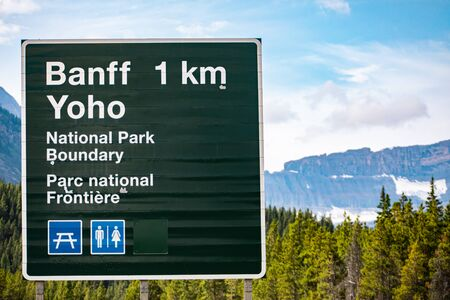 Canadian two languages French and English Information road green signs, 1 km to Banff Town, Yoho national park boundary, with symbols, Alberta, Canada