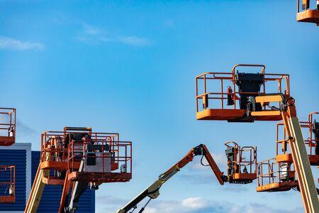 Un groupe de nacelles élévatrices surélevées, de plates-formes de travail élévatrices, est vu dans un état élevé dans un stockage, des grues mobiles hydrauliques avec espace de copie Banque d'images