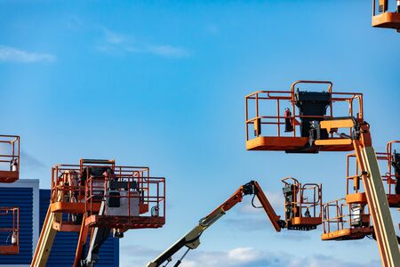 Un grupo de recolectores de cerezas elevadas, plataformas de trabajo aéreo, se ven en un estado elevado en almacenamiento, grúas móviles hidráulicas con espacio de copia Foto de archivo