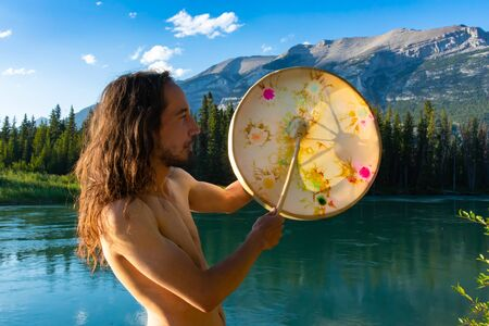 A closeup and side profile view of a slim man with dark wavy hair playing a sacred drum by a turquoise lake in Rocky Mountains, embracing spirituality