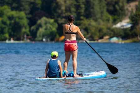 View from back to the athletic woman with kid during paddle-boarding in sports clothing. Young mom teaching son paddle boarding. Active summer holidays