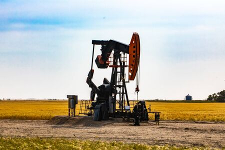 A lonely pumpjack, overground apparatus of a mechanical oil well, is seen by a large crop field in Saskatchewan, Canada. With copy space to both sides