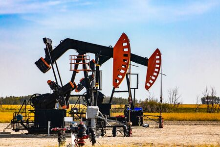 Details of two oil wells in rural Canada. Aka nodding horses, donkeys, pumps. Counterweight and crank with walking beam. Finite resource mining Stock Photo