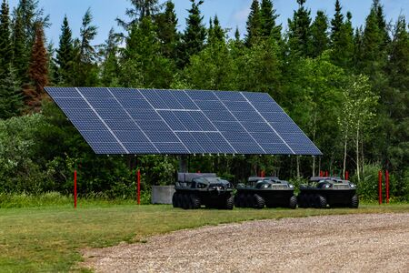 All terrain electric buggies are seen parked beneath large solar panels, futuristic renewable clean energy against a green pine forest with copy space