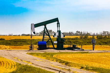 A wide view of a pumpjack in farmland. Finite resource mining. Gasoline, oil, petroleum, diesel, gas production. Carbon emissions and pollution.