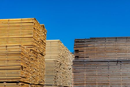 An abundance of timber planks are seen stored in a sawmill yard. Manufacture of natural building materials in British Columbia, Canada. With Copy space