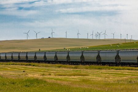 Row of metallic wagons of a Canadian freight train running between green fields in the countryside. Wind turbines in the background.