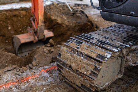 Una vista de cerca de la banda de rodadura continua de una miniexcavadora en el trabajo en un sitio de construcción, utilizando un brazo hidráulico para cavar un agujero con espacio de copia a la izquierda Foto de archivo