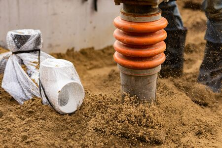 Close up details of a man operating rammer, aka a tamper, at work on a construction site, compacting the ground after the installation of sewerage