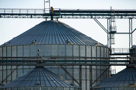 Closeup view of a large scale agrarian facility, large steel silos are seen with pipes, access ladders and scaffolding. Modern grain farming in Canada
