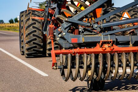 Closeup details of a tractor operated rotary tillage and plow device, steel rotating blades till vegetables. Driving in rural Alberta, Canada. With copy space
