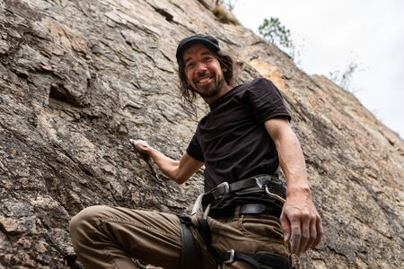 A low angle portrait of a happy thrill seeking caucasian man during a rock climbing adventure. Slim build male hanging from steep crag with copy space