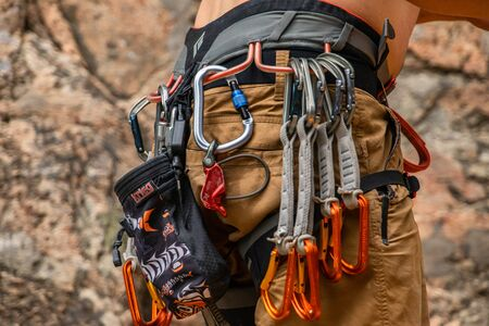 A closeup and detailed view of professional rock climbing equipment secured to the belt of a climber, various size clamps and belay devices for safety Banque d'images