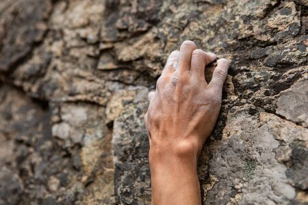 A close up shot on the fingers of a male rock climber, struggling to find a stable grip position on steep crag. Hold positions in natural stone cracks Фото со стока