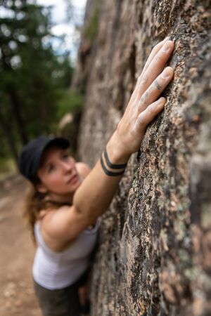 A selective focus view of a healthy woman ascending a limestone crag during a free solo competition, technical outdoor rock climbing with copy space
