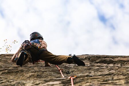 A low angle view of a rock climber in action, wearing kit belt with belay devices and safety clamps, climbing high on jagged stone, with copy space