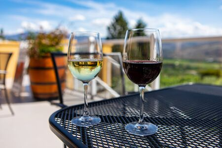 a couple of glasses of white and red wine on the table in selective focus. close up view against patio terrace with green vineyard landscape background Standard-Bild