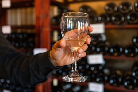 A glass of white wine on a man hand selective focus close up view against wine bottles on storage racks shelves, tasting room wines display background