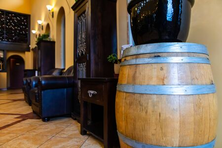 winery shop and tasting room interior furniture and decor, old oak brown wooden traditional barrel with black couches in the background Stock Photo
