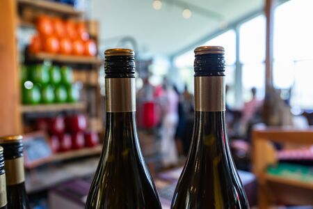 two bottles of wine top, with black and golden screw cap seal color, neck and shoulder of the bottle closeup selective focus, wines shop background Standard-Bild