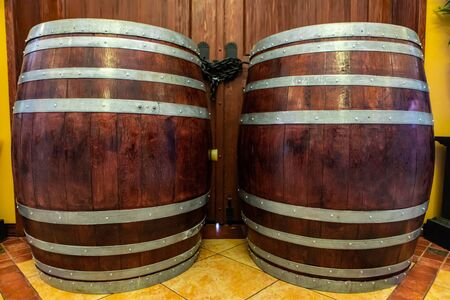 two old big oak brown wooden traditional barrels with iron rings, wine aging, beer, alcohol drink storage, winery tasting room interior decor