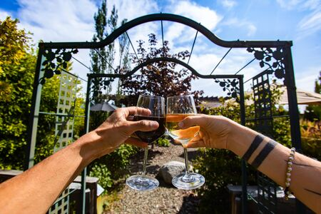 couple hands toasting and cheering red and white wine glasses in the front of a winery garden gate, tasting restaurant patio in the background